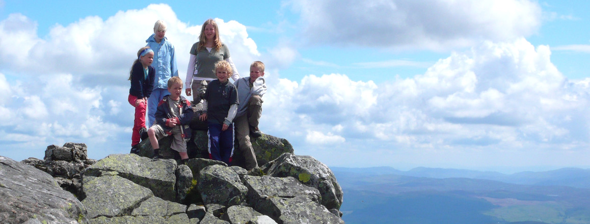 Family with young children on rocky hilltop in Scotland