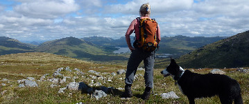 Hill walker and dog enjoying the view in the Scottish Highlands