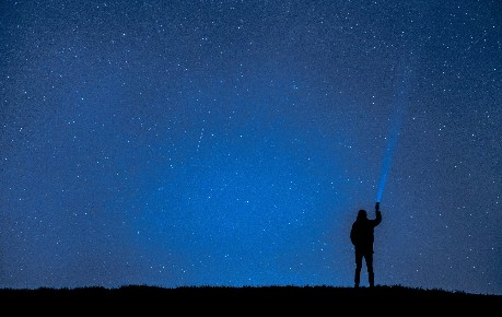 Man shining torch into star-filled sky