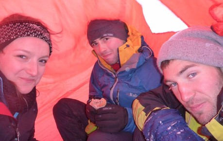 Climbers take shelter under a bothy bag