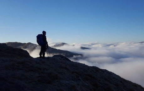 Mountaineer silhouetted against blue sky above cloud inversion